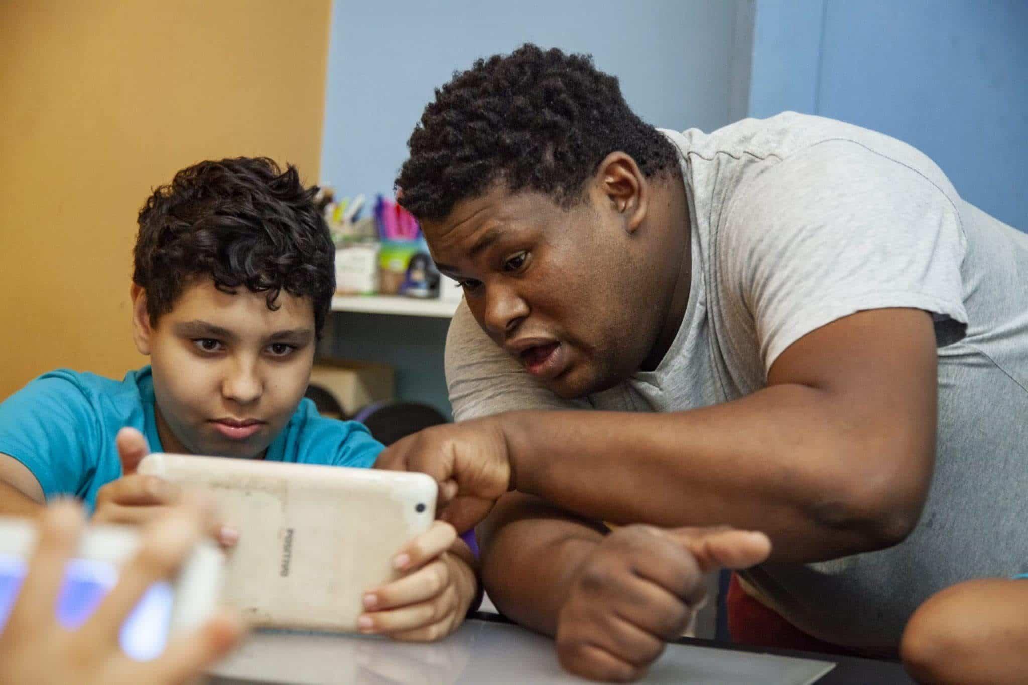 Educador Diego da Mata ensinando jovem no tablet